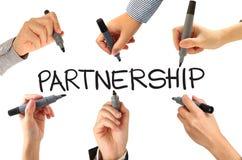 Viele Hände, die Partnerschaftswort schreiben Lizenzfreie Stockfotos