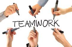Viele Hände, die Teamwork-Wort schreiben Lizenzfreie Stockbilder