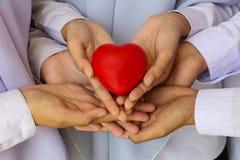 Viele Hände und ein rotes Herz Stockfotografie