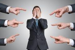 Viele Hände zeigen auf schuldigen Mann und tadeln ihn stockfotos