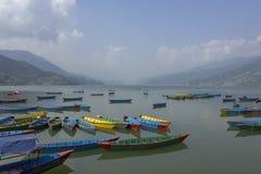 Viele hellen mehrfarbigen leeren hölzernen Boote auf dem Phewa See auf dem Hintergrund eines grünen Gebirgstales im Dunst lizenzfreie stockfotos