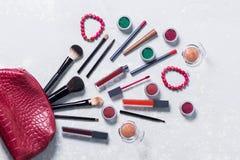 Viele hellen schönen Berufskosmetik geht Geldbeutel auf einem Hintergrund des weißen Lichtes, Bürste, Lippenstift, Schattenlidsch lizenzfreie stockbilder