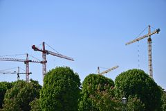 Viele industriellen Kräne des Hochhauses auf Hintergrund des blauen Himmels und der grünen Bäume stockfotos