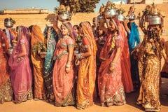 Viele jungen Frauen in den bunten Kleidern in der Menge des traditionellen Wüsten-Festivals Lizenzfreie Stockfotos