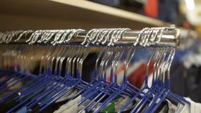 Viele Kleiderbügel im Bekleidungsgeschäft stock footage