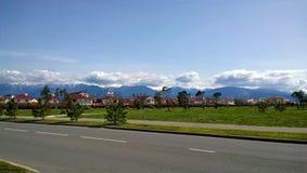 Viele kleinen netten Häuser auf einem Hintergrund von schönen Bergen Lizenzfreie Stockfotos