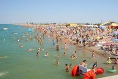 Viele Leute, die auf dem Strand sich entspannen Lizenzfreie Stockbilder