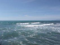 Viele Leute, die auf Surfbretter im Meer nahe Stärke dei marmi, Italien surfen stockbild