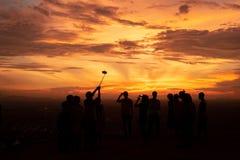 Viele Leute genießen nehmen Bild zusammen ihren an Sonnenuntergangberg lizenzfreie stockbilder