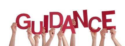 Viele Leute-Hände, die rote Wort-Anleitung halten lizenzfreie stockfotografie