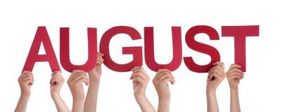 Viele Leute-Hände, die rotes gerades Wort August halten Lizenzfreie Stockbilder