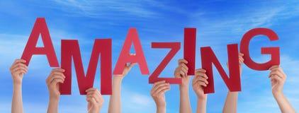 Viele Leute-Hände halten rotes Wort-erstaunlichen blauen Himmel Lizenzfreies Stockfoto