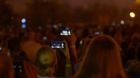 Viele Leute sind am musikalischen Ereignis und zuhause machen Fotos unter Verwendung der Smartphones stock footage