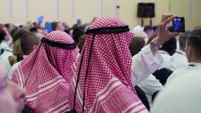 Viele Leute von verschiedenen Nationalitäten bei der Konferenz, welche die Darstellung betrachtet ablage Zwei arabische Männer im stock video