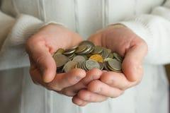Viele Münzen in den Händen von Männern, Reichtum symbolisierend Lizenzfreie Stockfotos