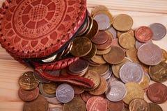 Viele Münzen, die um lederne Geldbörse liegen Stockfoto