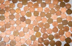 Viele Münzen, die am weißen Tisch lokalisiert liegen Lizenzfreies Stockfoto