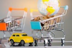 Viele Münzen, global im kleinen Warenkorb auf Tablette und gelbem c lizenzfreie stockbilder
