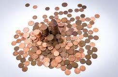 Viele Münzen am weißen Hintergrund werden verschüttet und stapeln Stockfoto