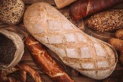 Viele mischten gebackene Brote und Rollen auf rustikalem Holztisch Stockbild