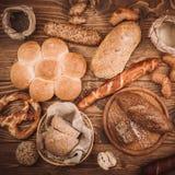 Viele mischten gebackene Brote und Rollen auf rustikalem Holztisch Lizenzfreie Stockbilder