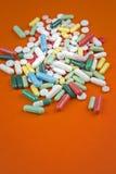 Viele Pillen auf orange Hintergrund Stockbilder