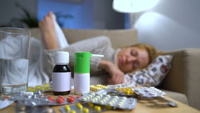 Viele Pillen und Medizin auf einer Tabelle in Front Of eine kranke junge Frau auf Couch stock video footage