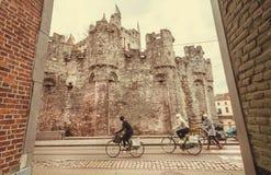 Viele Radfahrer, die hinter das des 12. Jahrhundertsgravensteen-Ziegelsteinschloss und die alten Backsteinhäuser fahren Lizenzfreie Stockbilder