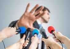 Viele Reporter notieren mit Mikrophonen einen Politiker, der keine Kommentargeste zeigt lizenzfreie stockbilder