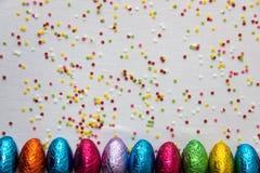 Viele richteten farbige SchokoladenOstereier auf wei?em Hintergrund und bunten Konfettis aus lizenzfreie stockfotos