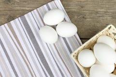 Viele rohen Hühnereier im Weidenkorb und drei Eier auseinander auf altem Weinleseholztisch lizenzfreie stockfotos