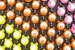 Viele rosa, orange, gelben Wecker auf dem Wandhintergrund Lizenzfreies Stockfoto