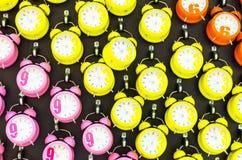 Viele rosa, orange, gelben Wecker auf dem Wandhintergrund lizenzfreie stockbilder