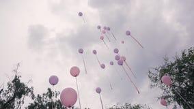 Viele rosa purpurroten Ballone fliegen in den Himmel am Hochzeitstag draußen stock footage