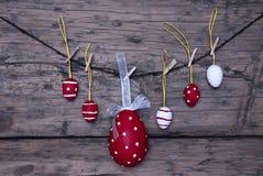 Viele roten und weißen Ostereier und ein großes Ei, die an der Linie hängen Lizenzfreie Stockbilder