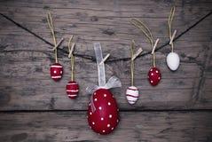 Viele roten und weißen Ostereier und ein großes Ei, die an der Linie Rahmen hängen Stockfotografie