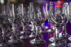 Viele saubere leere Gläser Getränke auf der Bar in einem Nachtklub Greller Glanz und Reflexionen auf den Gläsern in der Dunkelhei lizenzfreie stockfotos