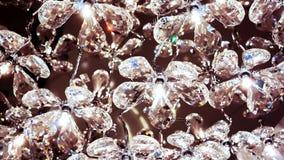 Viele sauberen Diamantkristallblumen legen eins nach dem anderen mit Licht nach innen als Teil des Luxusleuchters Lizenzfreie Stockfotos
