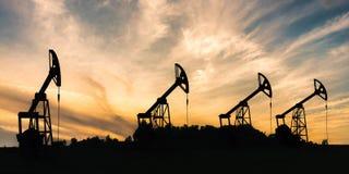 Viele Schattenbilder von Bohrölanlagen bei Sonnenuntergang Stockfotos