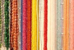 Viele schimmernden Halsketten gemacht mit bunten Steinen für Verkauf herein Lizenzfreie Stockbilder