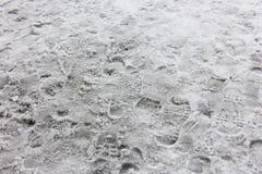 Viele shoeprints im schmutzigen Schnee Stockfotos