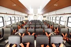 Viele Sitze rudern innerhalb der Luxuskreuzfahrtfähre mit orange Schwimmweste lizenzfreie stockbilder