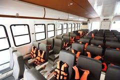 Viele Sitze rudern innerhalb der Luxuskreuzfahrtfähre mit orange Schwimmweste lizenzfreies stockbild