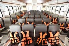 Viele Sitze rudern innerhalb der Luxuskreuzfahrtfähre mit orange Schwimmweste stockbild