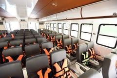 Viele Sitze rudern innerhalb der Luxuskreuzfahrtfähre mit orange Schwimmweste stockfotografie