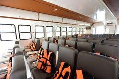 Viele Sitze rudern innerhalb der Luxuskreuzfahrtfähre mit orange Schwimmweste stockbilder