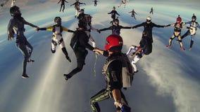 Viele Skydivers machen Bildung im bewölkten Himmel Extreme Bremsung Schwestern, die Hände anhalten drehzahl stock video