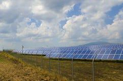 Viele Sonnenkollektoren hinter rostigem Stacheldraht Stockfoto
