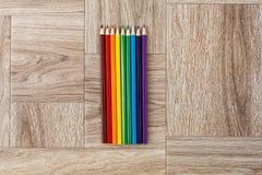 Viele sortierte Farben zeichnen auf hölzernem Hintergrund an Stockfotografie