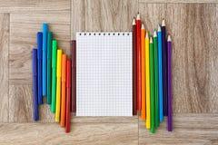 Viele sortierte Farbmarkierungsstifte und -bleistifte mit Notizblock Stockfotos